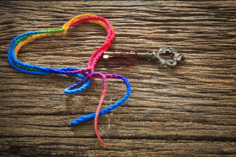 De de kleurrijke vorm en sleutel van het garenhart op houten geweven gebruik als achtergrond voor liefde ondertekenen in valentijn stock afbeelding