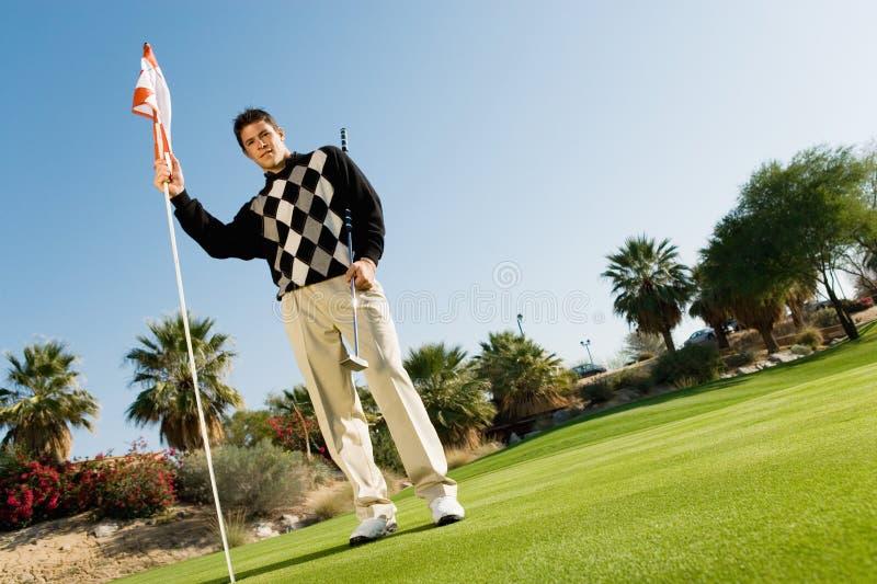 De de mannelijke Vlag en Golfclub van de Holding van de Golfspeler royalty-vrije stock fotografie