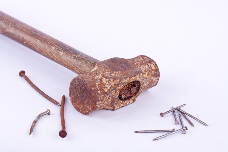 de de oude die hamer en roest van de roestslee nagelen kopspijker op wit geïsoleerd hulpmiddel wordt gebruikt als achtergrond royalty-vrije stock fotografie