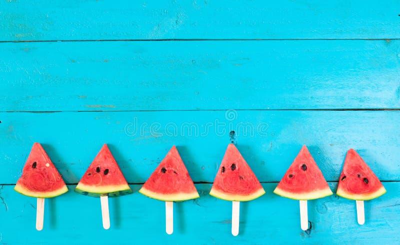 de de plakijslollys van de de zomerwatermeloen op een blauwe rustieke houten rug stock fotografie