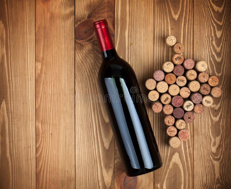 De de rode wijnfles en druif vormden kurken stock fotografie
