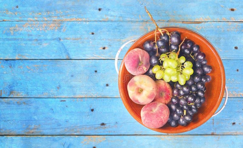 De de vlakke druiven en perziken, leggen op een rustieke lijst, goed exemplaar s stock afbeeldingen