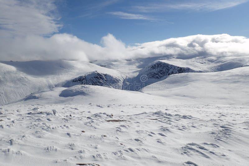 De de wintersneeuw behandelde mening van de Cairngorm-bergen op een heldere zonnige dag royalty-vrije stock afbeeldingen