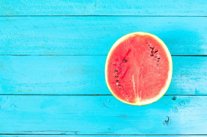 de de zomerwatermeloen is plak van de helft op blauwe rustieke houten bac royalty-vrije stock foto