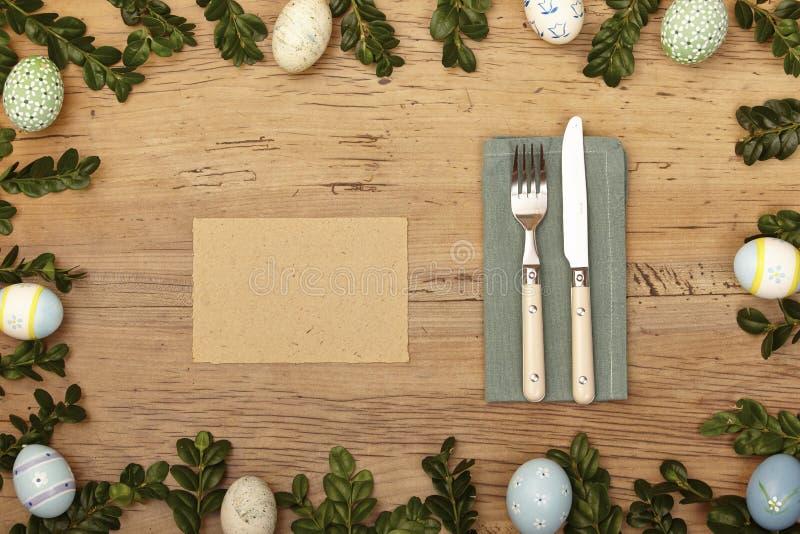 De decoratie, de spatie, de kaart, het servet, knive en de vork van Pasen op hout stock foto's