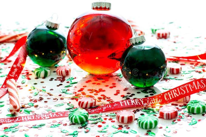 De decoratie met rode vloeistof vulde de bal van het Kerstmisornament en twee groene gevulde die ornamentballen door een rood heb stock afbeeldingen