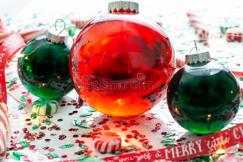 De decoratie met rode vloeistof vulde de bal van het Kerstmisornament en twee groene gevulde die ornamentballen door een rood heb royalty-vrije stock foto