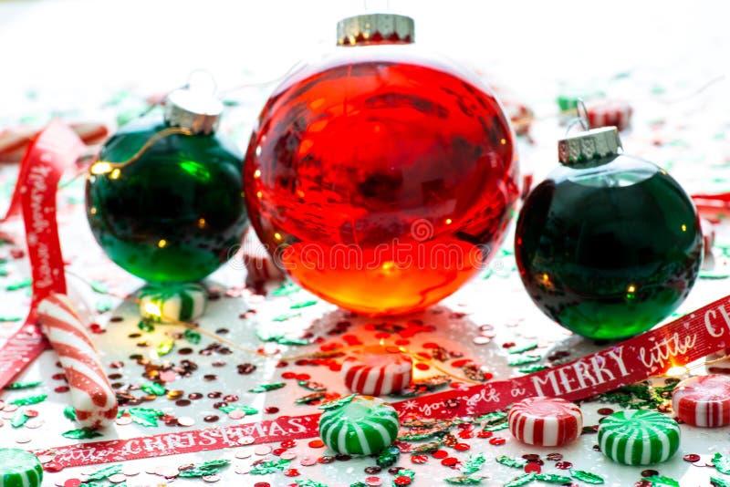 De decoratie met rode vloeistof vulde de bal van het Kerstmisornament en twee groene gevulde die ornamentballen door een rood heb stock foto