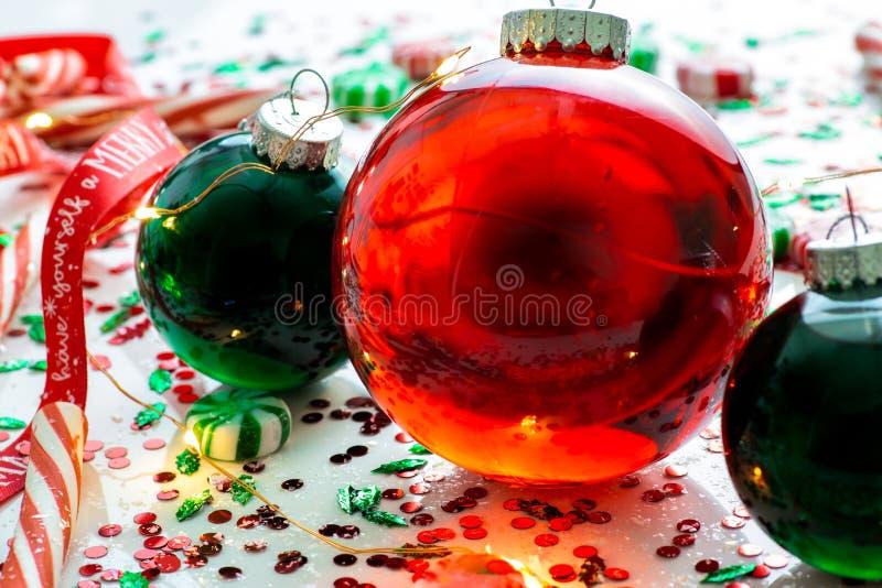 De decoratie met rode vloeistof vulde de bal van het Kerstmisornament en twee groene gevulde die ornamentballen door een rood heb stock foto's