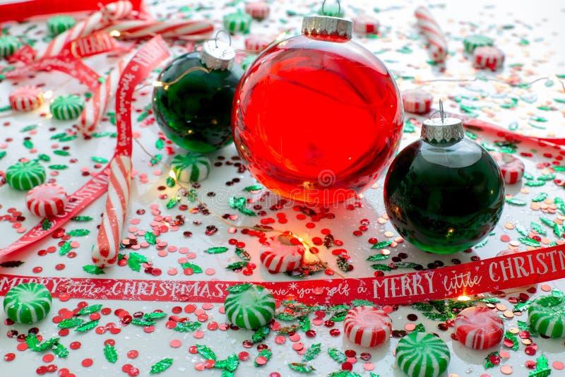 De decoratie met rode vloeistof vulde de bal van het Kerstmisornament en twee groene gevulde die ornamentballen door een rood heb stock fotografie