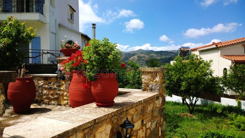 De decoratie op Griekse straat - de grote heldere potten en de geraniums van de kleibloem daarin stock afbeelding