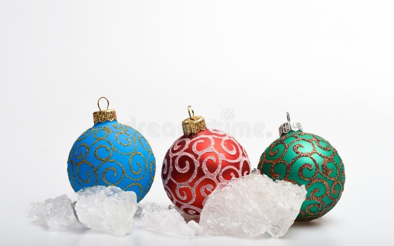 De decoratie van drie die Kerstmisballen dichtbij stenen van ijs op wit wordt geïsoleerd De winter en vorstconcept Bevroren stukk royalty-vrije stock foto's