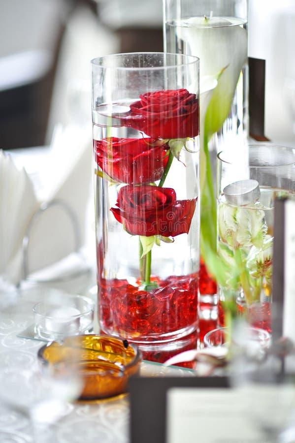 De decoratie van het luxehuwelijk met rode rozen in een glas stock foto