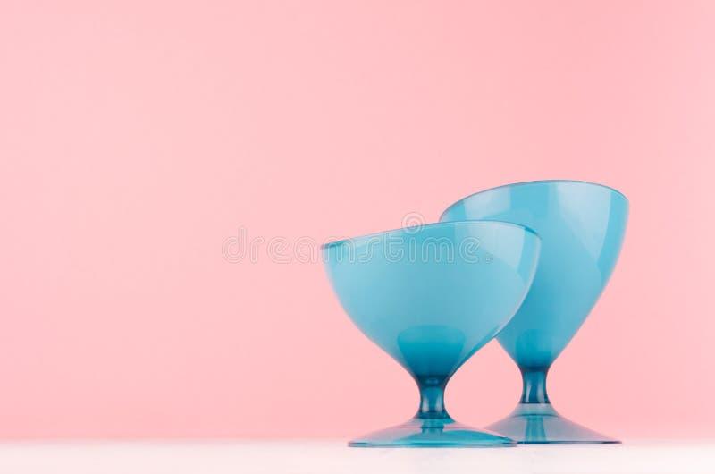 De decoratie van het Minimalistichuis - de glanzende blauwe plastic vaas van de eivorm op witte houten raad en pastelkleur roze a royalty-vrije stock foto's