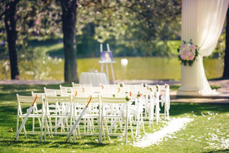 De decoratie van de huwelijksceremonie met stoelen en boog dichtbij het meer Openluchthuwelijksceremonie bij de zomerpark royalty-vrije stock foto