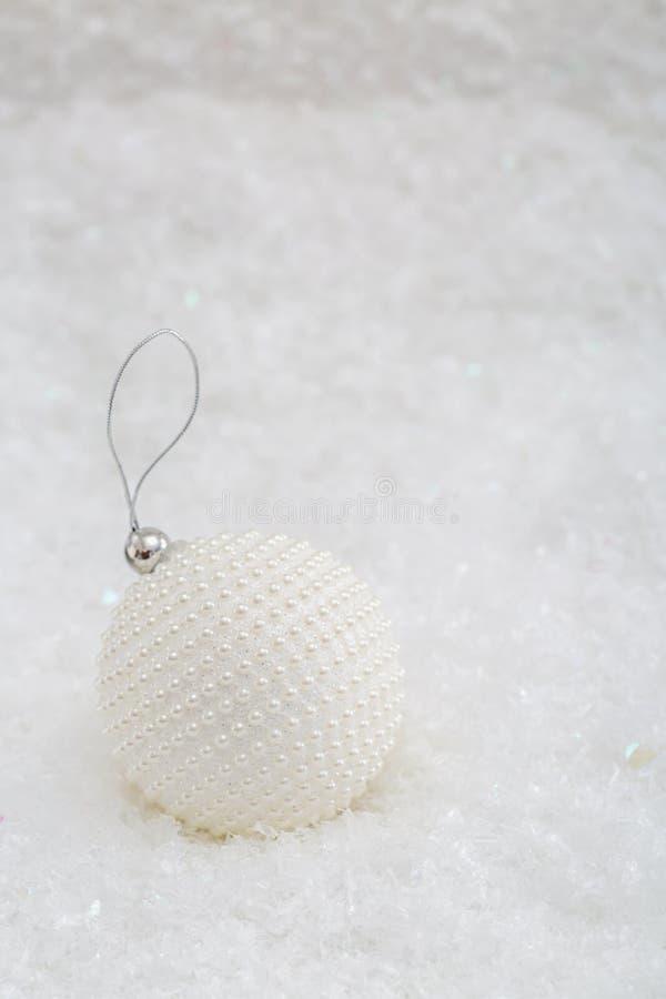 De decoratie van Kerstmis De witte parels van het balpaarlemoer op een sneeuw en een mooie vage achtergrond van het schitteren bo royalty-vrije stock afbeelding