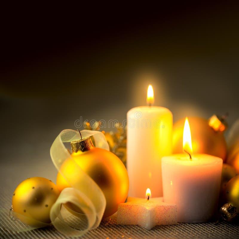 De Decoratieachtergrond van avondkerstmis met kaarsen, snuisterijen en linten stock afbeeldingen