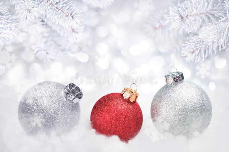 De Decoratieachtergrond van de de wintervakantie Kerstmisballen onder Sparrentakken met Vorst en Sneeuw worden behandeld die royalty-vrije stock afbeelding