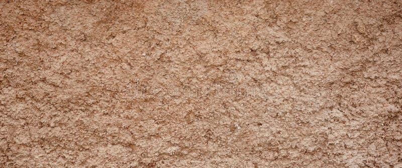 De decoratieve Bruine Gekleurde Korrelmuur Brede Backgr van het Cementpleister stock foto's