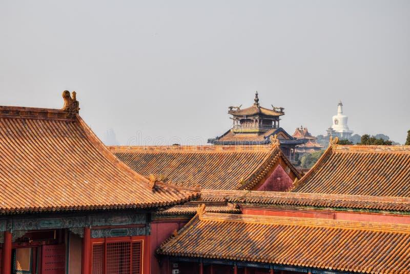 De decoratieve daken van Verboden Stad met de Witte pagode in Beihai-park op de achtergrond, Peking, China stock fotografie