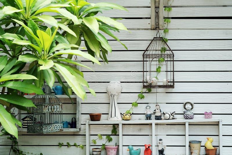 De decoratieve muur met plank maakt van wit hout op de achtergrond van de tuintextuur stock foto