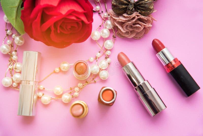 De decoratieve vlakte legt samenstelling met kleurrijke lippenstift, parel en bloemen royalty-vrije stock afbeeldingen