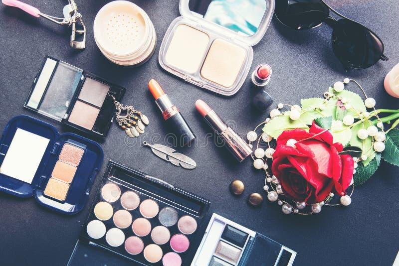 De decoratieve vlakte legt samenstelling met kleurrijke lippenstift, parel en bloemen stock foto