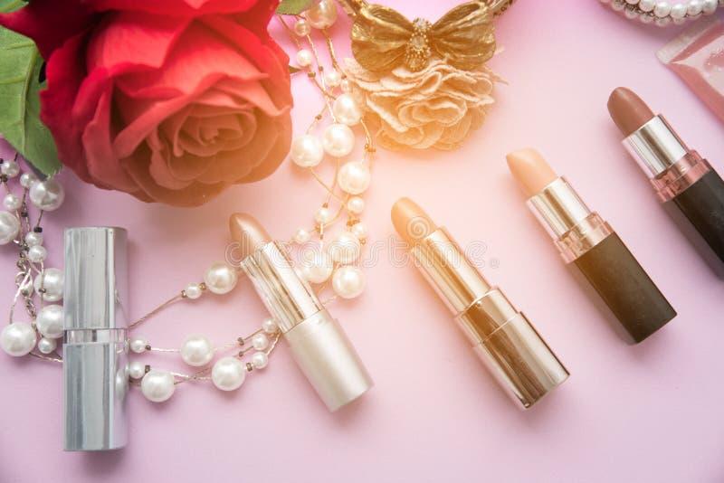 De decoratieve vlakte legt samenstelling met kleurrijke lippenstift, parel en bloemen stock afbeeldingen