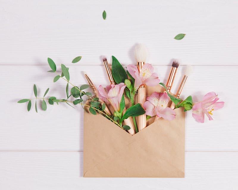 De decoratieve vlakte legt samenstelling met make-upproducten, kraftpapier-envelop en bloemen Vlak leg, hoogste mening over witte stock afbeelding