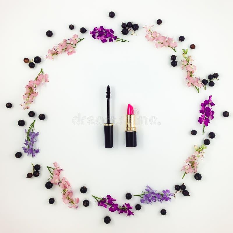 De decoratieve vlakte legt samenstelling met schoonheidsmiddelen, bloemen en bessen stock foto's