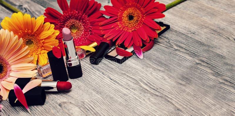 De decoratieve vlakte legt samenstelling met schoonheidsmiddelen en bloemen Witte achtergrond royalty-vrije stock afbeelding