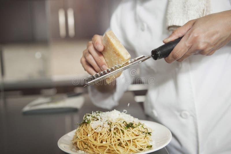 De Deegwaren van chef-kokgrating cheese onto in Keuken stock foto's