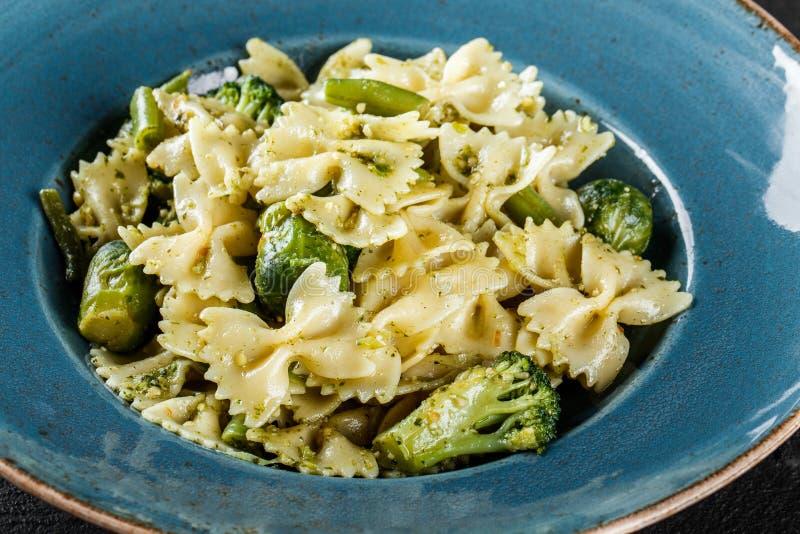 De deegwaren van veganistfarfalle in een spinaziesaus met broccoli, spruitjes, slabonen in plaat op donkere steenachtergrond royalty-vrije stock foto's