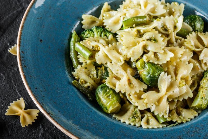 De deegwaren van veganistfarfalle in een spinaziesaus met broccoli, spruitjes, slabonen in plaat op donkere steenachtergrond stock afbeelding