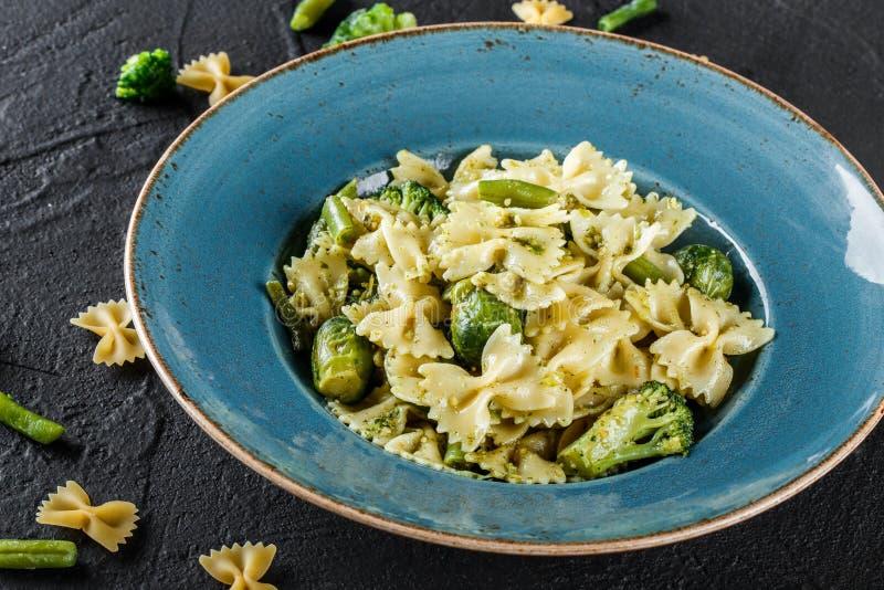 De deegwaren van veganistfarfalle in een spinaziesaus met broccoli, spruitjes, slabonen in plaat op donkere steenachtergrond hoog royalty-vrije stock fotografie