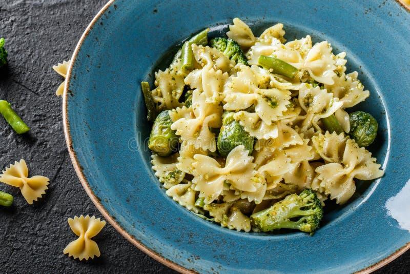 De deegwaren van veganistfarfalle in een spinaziesaus met broccoli, spruitjes, slabonen in plaat op donkere steenachtergrond hoog stock foto's