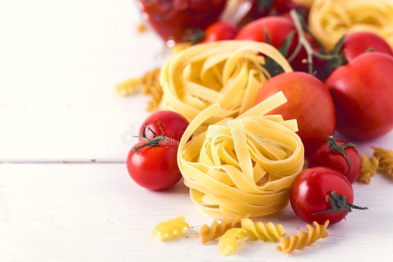 De deegwarenproducten met van de Deegwarenfusili Fettuccine van de Tomatenkaas de Ruwe van het de Ingrediënten Italiaanse Voedsel royalty-vrije stock foto's
