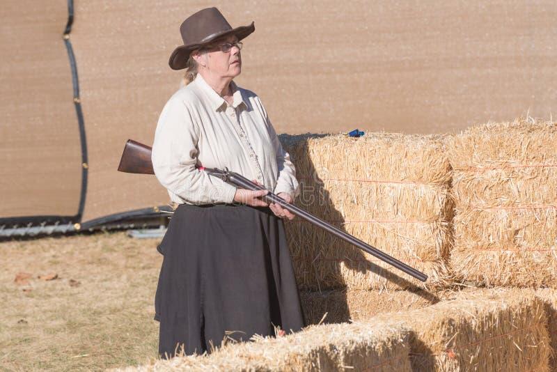 De deelnemer kleedde zich in kostuum van de periodecowboy, die gunfig het afbeelden royalty-vrije stock foto's
