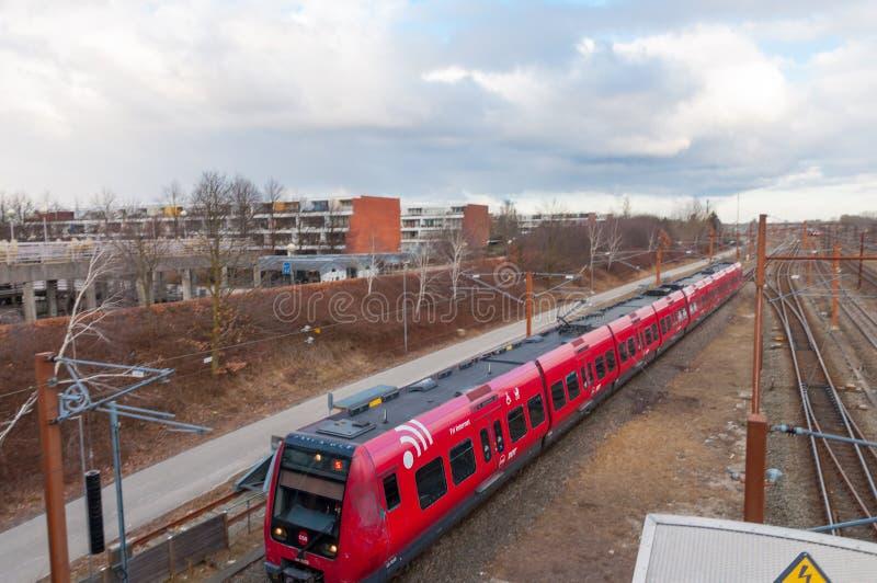 De Deense lokale trein komt aan het station van Hoje Taastrup in Denemarken aan stock afbeeldingen