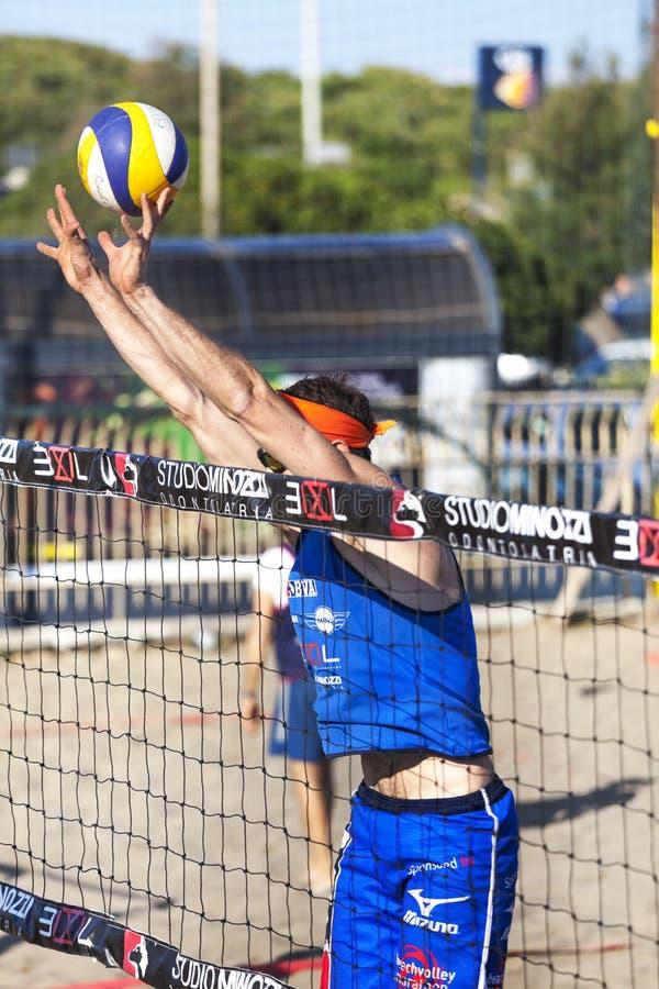 De defensie van het het strandvolleyball van de atletenmens Muur op het net Wapens omhoog royalty-vrije stock afbeelding