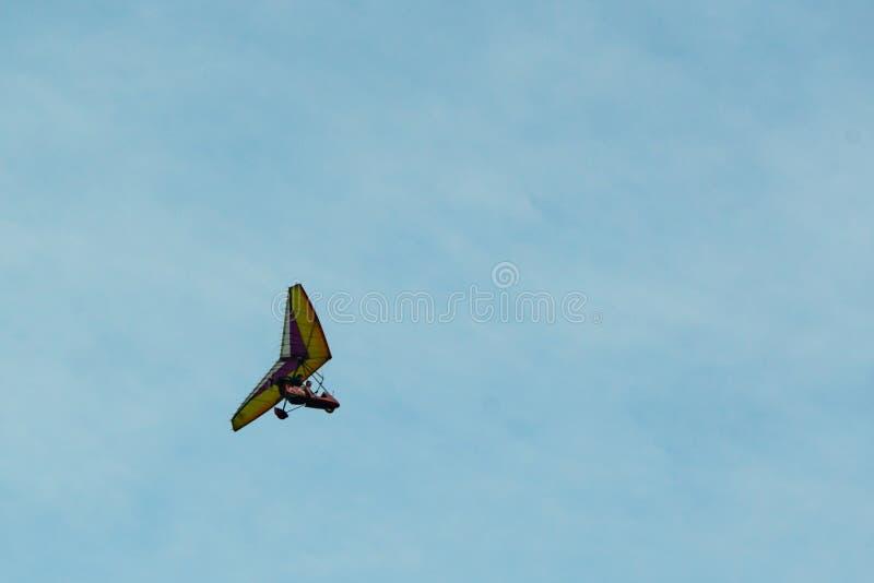 De deltavlieger op een blauwe hemel als achtergrond met lichte wolken Het vliegen van een gyroplane stock fotografie