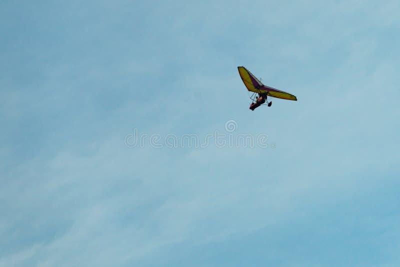 De deltavlieger op een blauwe hemel als achtergrond met lichte wolken Het vliegen van een gyroplane royalty-vrije stock afbeeldingen