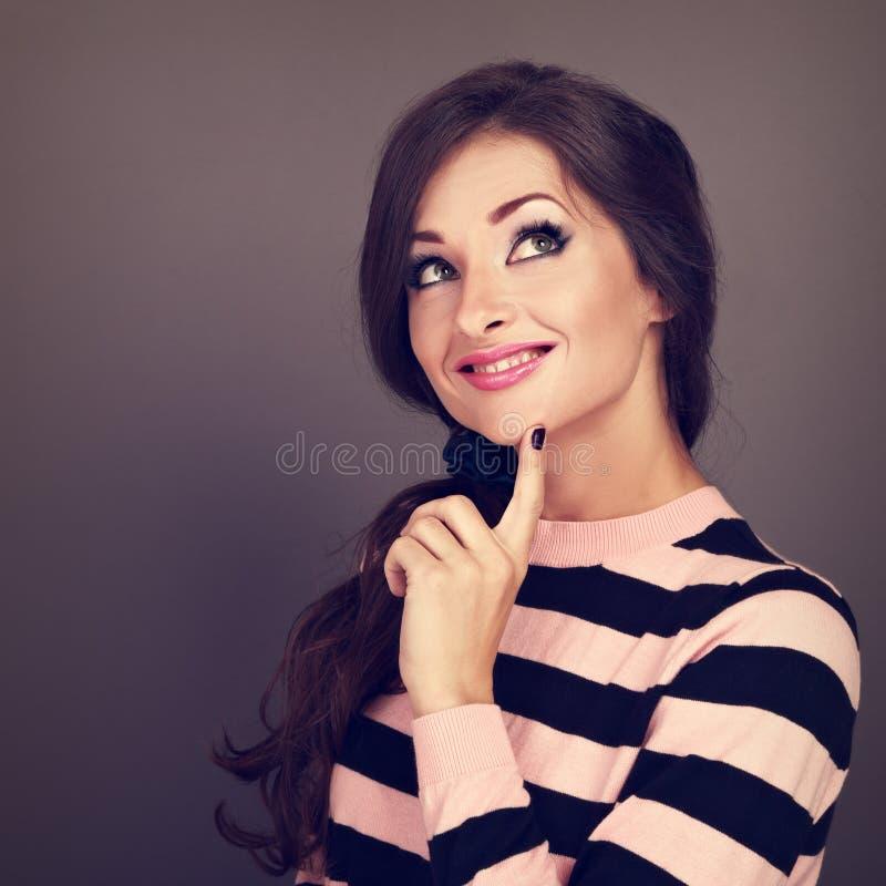 De denkende toevallige mooie krullende vrouw die van de haarstijl omhoog kijken met royalty-vrije stock afbeelding