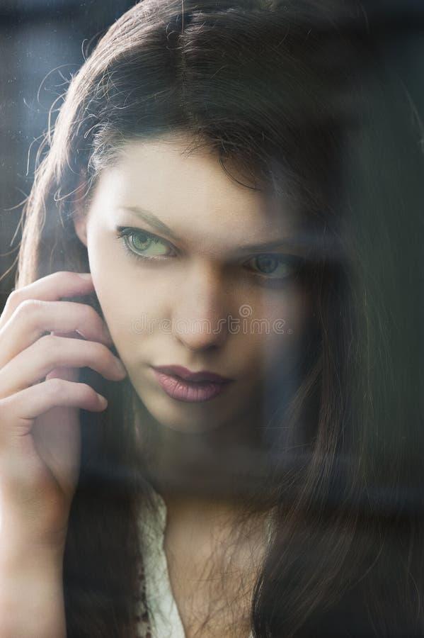 De denkende vrouw bij venster potrayed in close-up stock afbeelding