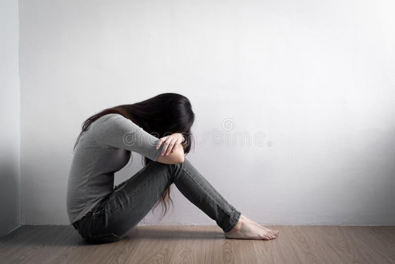 De depressievrouw zit op vloer stock afbeeldingen