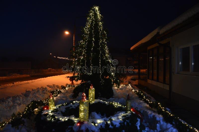 De derde kaars van Komst zette en decoratied Kerstboom aan royalty-vrije stock afbeeldingen