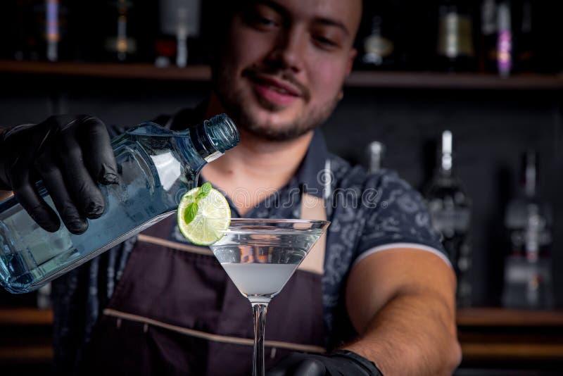 De deskundige barman maakt cocktail bij nachtclub Professionele barman aan het werk in bar die zoete drank gieten in glas stock afbeelding
