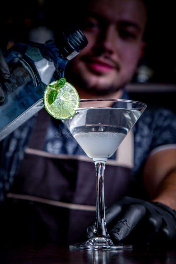 De deskundige barman maakt cocktail bij nachtclub Professionele barman aan het werk in bar die zoete drank gieten in glas stock foto's