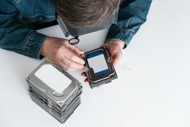 De deskundige computerhersteller met meer magnifier op zijn hoofd is kenmerkend hardeschijfstation in workshop stock foto's