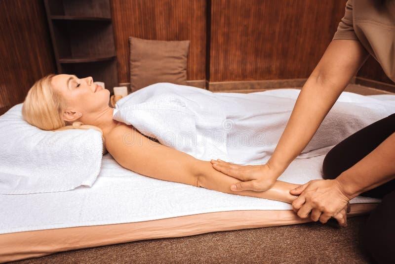 De deskundige masseuse die van Nice haar cliëntenhand houden royalty-vrije stock afbeeldingen